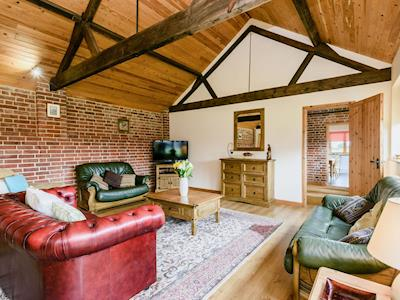 Spacious beamed living room with wooden floor and exposed walls | Monks Barn, Langley, Norwich