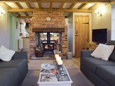 Living room with beamed ceiling & wood burner | Russell Green Cottage, Wilby, near Eye