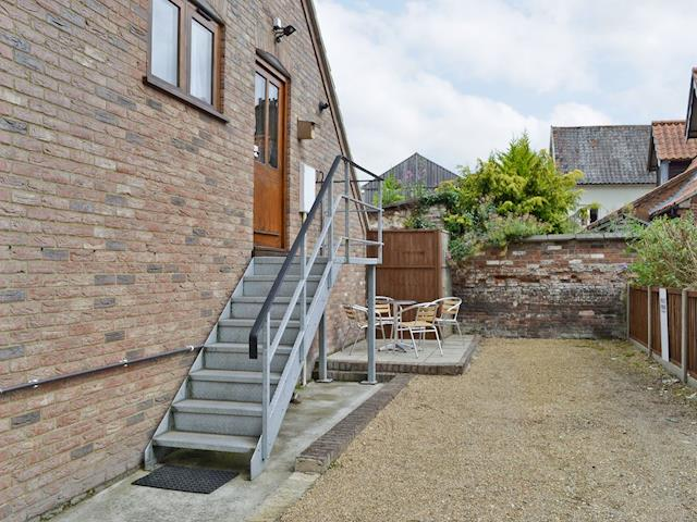 Gravelled courtyard and entrance to holiday home via steps | Kingfisher, Wells-next-the-Sea