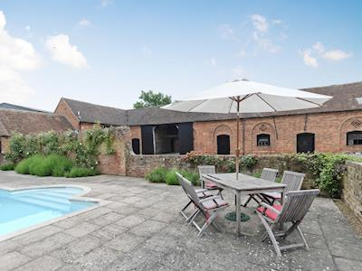 Exterior with pool & seating area | The Stables at Southfield House, Forthampton, near Tewkesbury