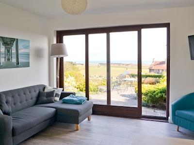 Light and airy lounge area with sliding patio doors | Eider Cottage, Embleton