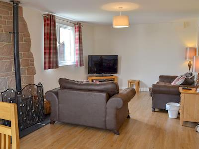 Lovely and welcoming living area with wood burner | The Old Parish Hall, Seahouses, near Alnwick