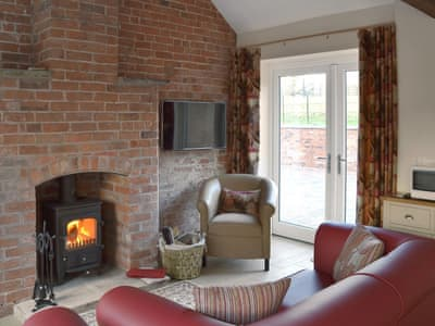 Cosy living area with wood burner | Carpenters Cottage - Betley Court Farm, Betley, near Nantwich