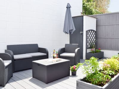 Stylish enclosed courtyard with outdoor furniture | Maybird Cottage, Hayle