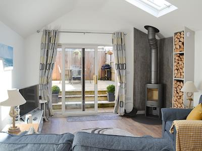 Cosy lounge area with wood burner & patio doors leading to the decking area | Little Tregarthen, Padstow