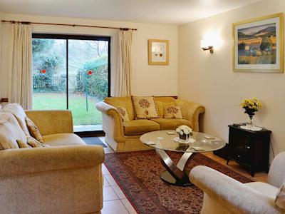The tile-floored living room has patio doors which open onto the garden | Corner Cottage - Croft Cottages, Watchet
