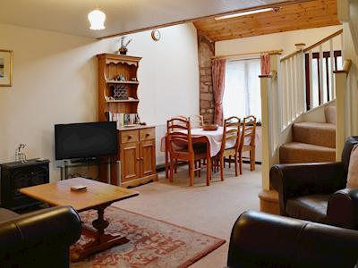 Comfortable elather suite, lcd tv and an electric 'woodburner' give the living/dining room a welcoming feel | Linhay 5 - Croft Cottages, Watchet