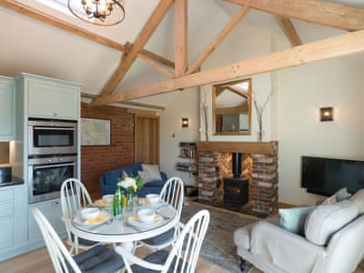 Open plan living with multi-fuel burner & wood beams | Daisy Cottage, Scruton, near Northallerton